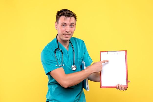 Vooraanzicht van de jonge mannelijke analyses van de artsenholding op gele muur Gratis Foto