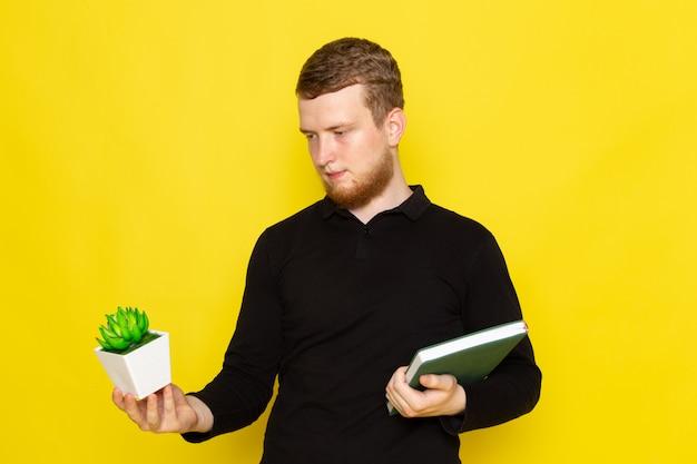 Vooraanzicht van de jonge mens die in zwart overhemd groene installatie en voorbeeldenboek houdt Gratis Foto