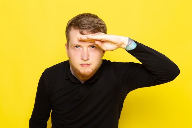 Vooraanzicht van de jonge mens in het zwarte overhemd stellen die de afstand onderzoeken Gratis Foto