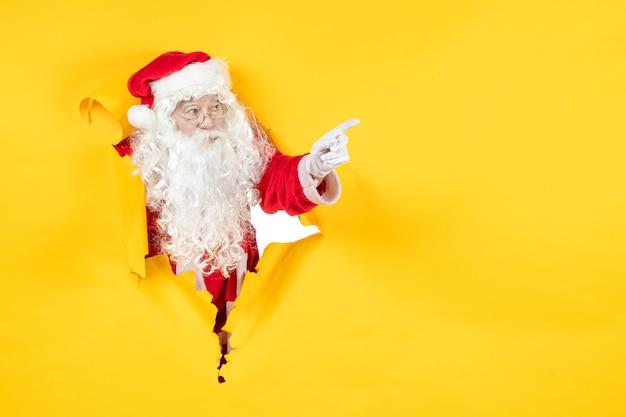 Vooraanzicht van de kerstman die door gescheurde document gele muur kijkt Gratis Foto