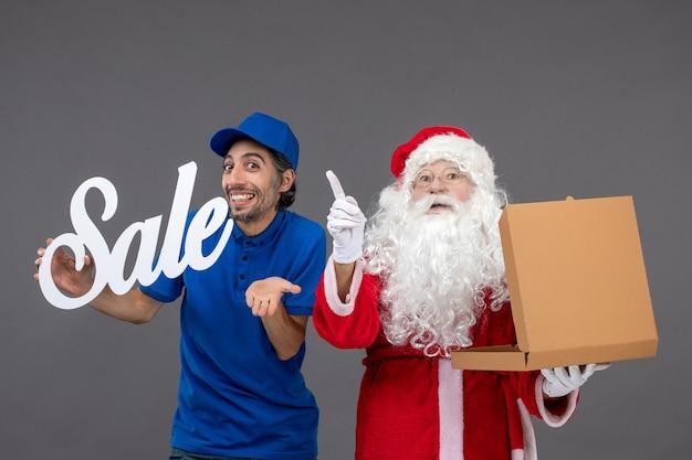 Vooraanzicht van de kerstman met mannelijke koeriersbedrijf verkoop banner en voedseldoos op de grijze muur Gratis Foto