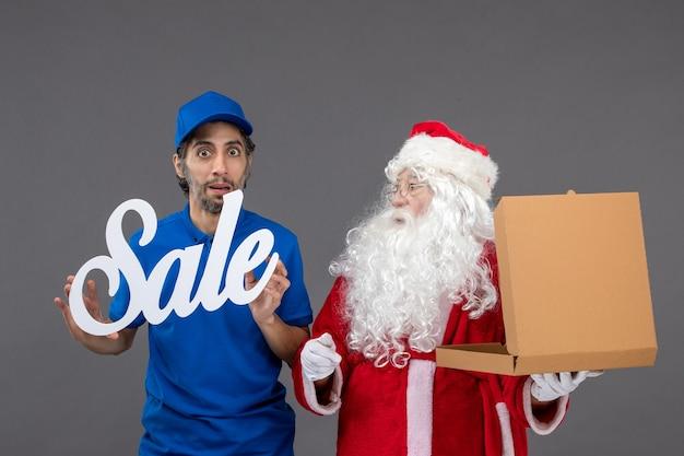 Vooraanzicht van de kerstman met mannelijke koeriersbedrijf verkoop banner en voedseldozen op de grijze muur Gratis Foto