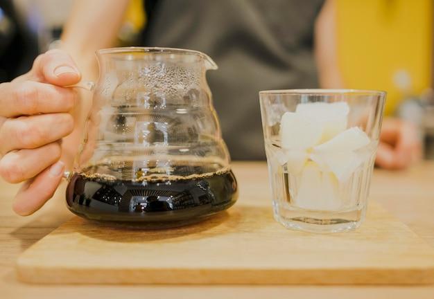 Vooraanzicht van de koffiepot van de baristaholding met glas ijs Gratis Foto