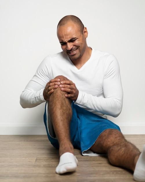 Vooraanzicht van de mens die aan kniepijn lijdt Gratis Foto