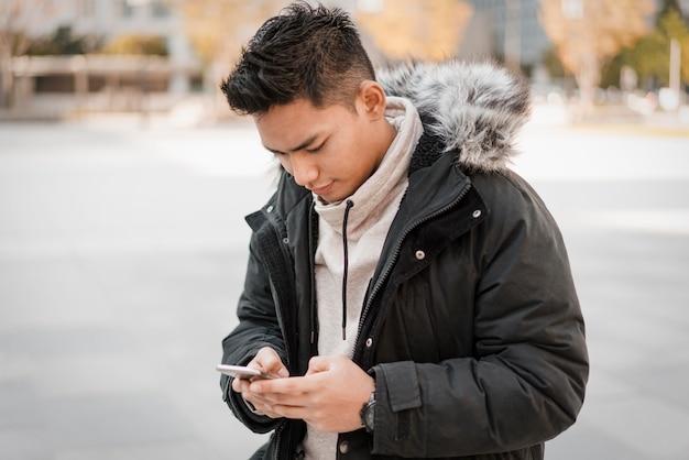 Vooraanzicht van de mens die smartphone buitenshuis gebruikt Premium Foto
