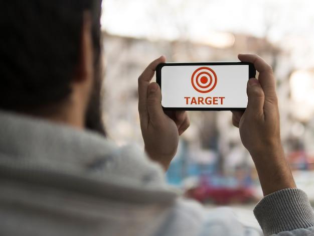 Vooraanzicht van de mens die smartphone met doel steunt Gratis Foto