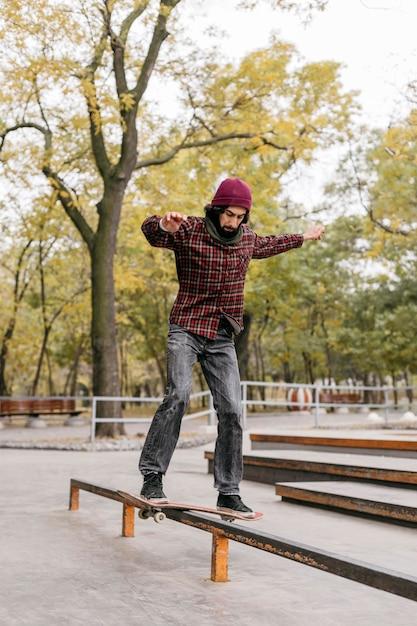 Vooraanzicht van de mens die trucs met skateboard buiten doet Gratis Foto