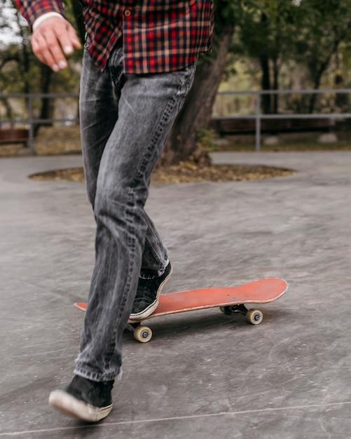 Vooraanzicht van de mens die trucs met skateboard buiten in het park doet Gratis Foto