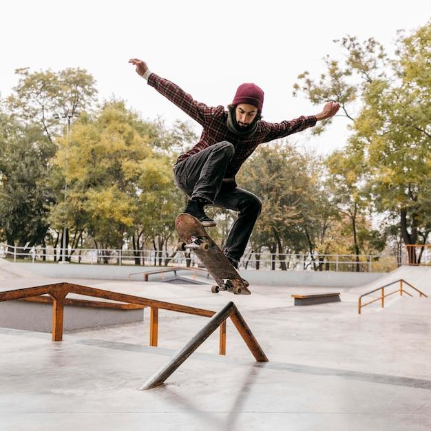 Vooraanzicht van de mens die trucs met skateboard buitenshuis doet Gratis Foto