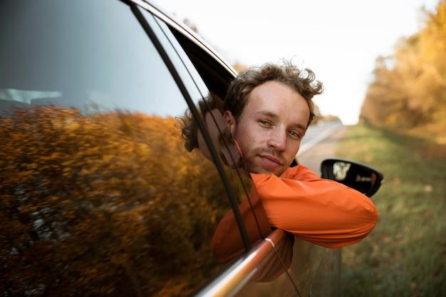 Vooraanzicht van de mens in de auto tijdens een roadtrip Premium Foto
