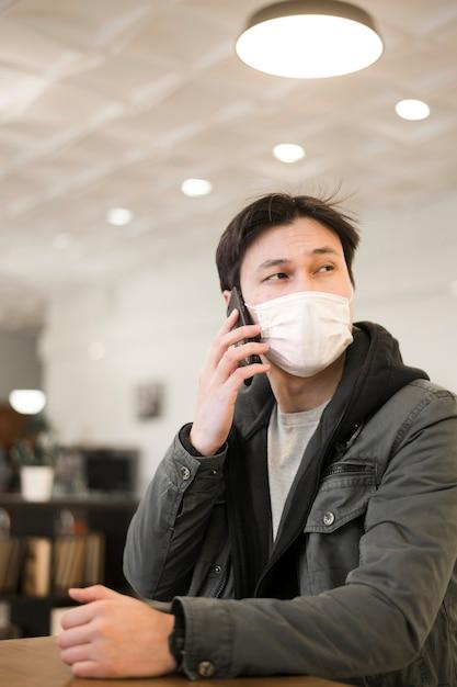 Vooraanzicht van de mens met medisch masker dat op smartphone spreekt Gratis Foto