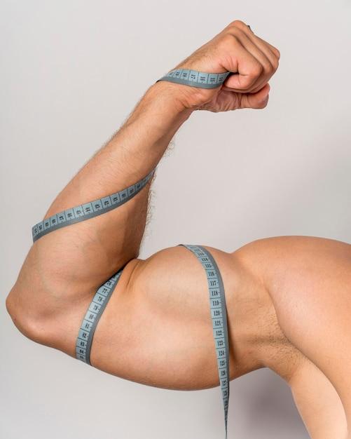 Vooraanzicht van de mens met meetlint over biceps en arm Gratis Foto
