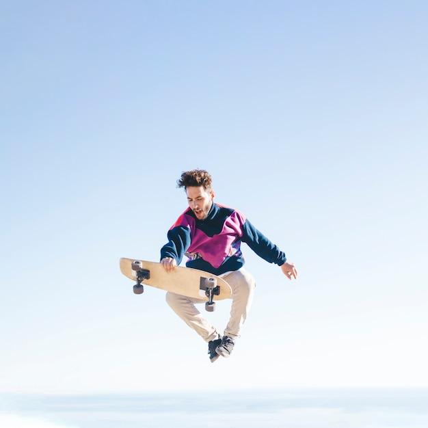 Vooraanzicht van de mens met skateboard in lucht Gratis Foto
