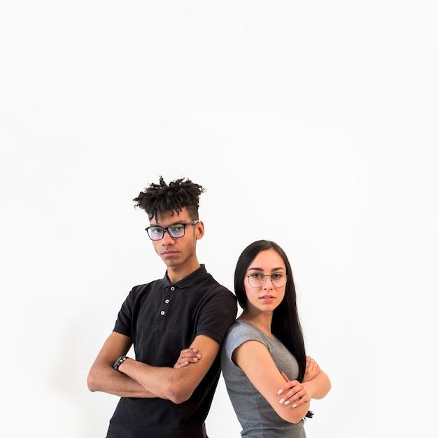 Vooraanzicht van de multi-etnische man en vrouw die camera bekijken die zich tegen witte achtergrond bevinden Gratis Foto