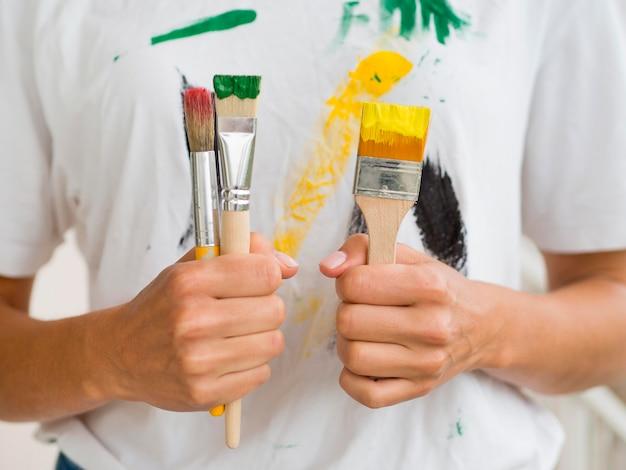 Vooraanzicht van de penselen van de persoonsholding Gratis Foto