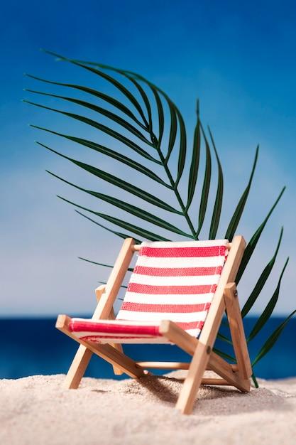 Vooraanzicht van de strandstoel op het strand met blad Premium Foto