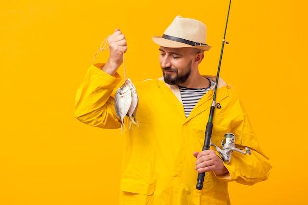 Vooraanzicht van de trotse vangst en de hengel van de vissersholding Gratis Foto