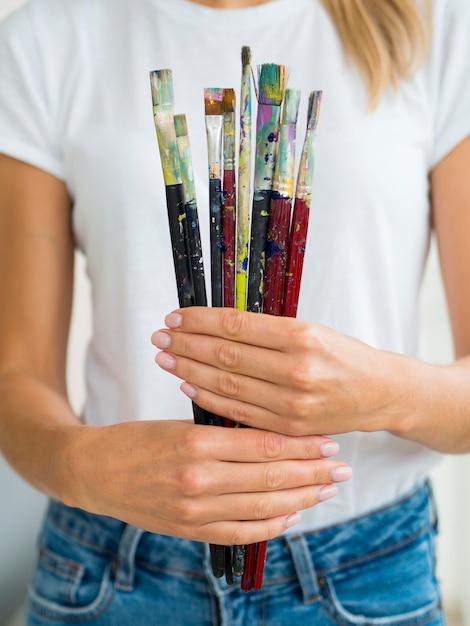 Vooraanzicht van de verfborstels van de vrouwenholding in handen Gratis Foto