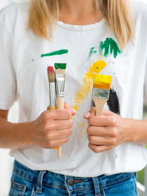 Vooraanzicht van de verfborstels van de vrouwenholding Gratis Foto