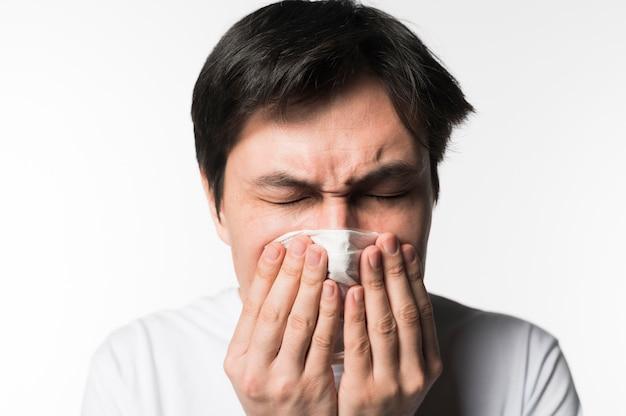 Vooraanzicht van de zieke man niezen in servet Gratis Foto