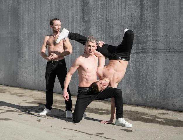 Vooraanzicht van drie shirtloze hiphopartiesten die tijdens het dansen buiten poseren Gratis Foto