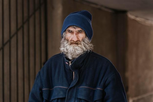 Vooraanzicht van een bebaarde dakloze man op straat Gratis Foto