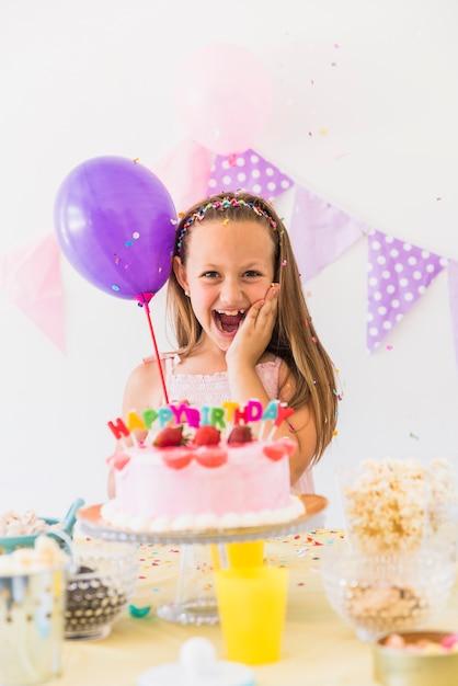 Vooraanzicht van een gelukkige ballon die van de meisjesholding van verjaardagsviering geniet Gratis Foto