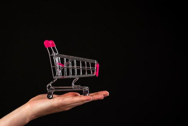 Vooraanzicht van een hand die een miniboodschappenwagentje op een zwarte achtergrond houdt Gratis Foto