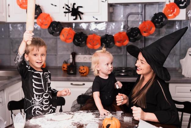 Vooraanzicht van een moeder en haar kinderen die halloween-koekjes maken Gratis Foto
