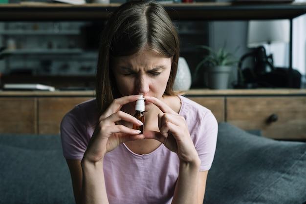Vooraanzicht van een zieke vrouw die neusnevel snuift Gratis Foto