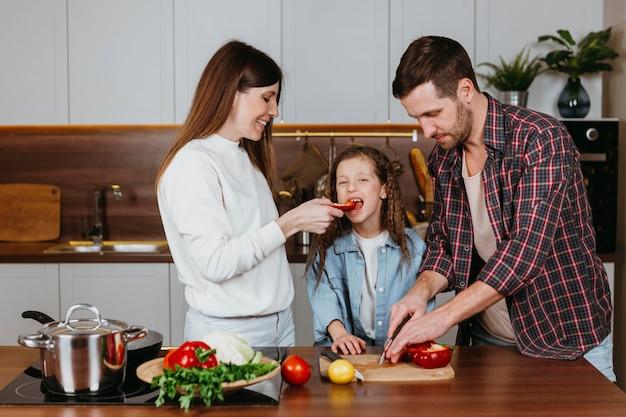 Vooraanzicht van familie die voedsel thuis voorbereidt Gratis Foto
