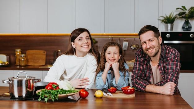 Vooraanzicht van familie poseren in de keuken Gratis Foto