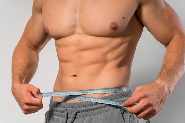 Vooraanzicht van fit man met meetlint rond de taille Gratis Foto