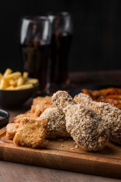 Vooraanzicht van gebakken kippenpoten met koolzuurhoudende dranken Gratis Foto