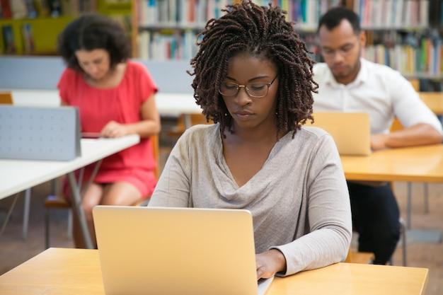 Vooraanzicht van geconcentreerde vrouw die met laptop bij bibliotheek werkt Gratis Foto