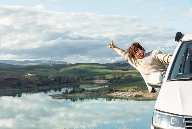 Vooraanzicht van gelukkig man genieten van de natuur tijdens een roadtrip Gratis Foto