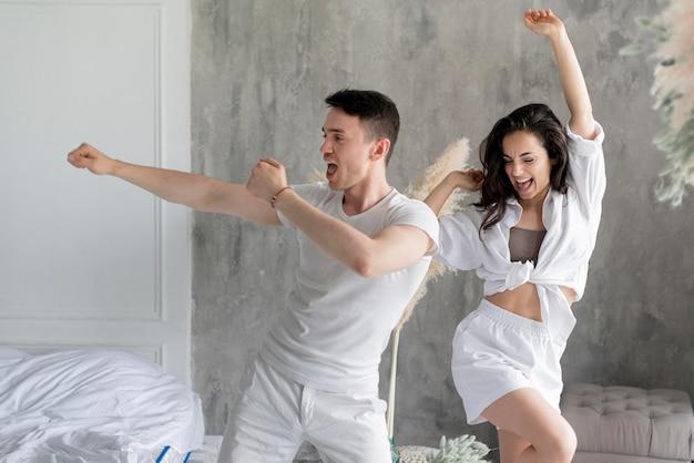 Vooraanzicht van gelukkig paar dat thuis danst Gratis Foto