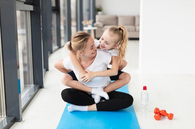 Vooraanzicht van gelukkige moeder en kind op yoga mat met gewichten Gratis Foto