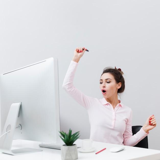 Vooraanzicht van gelukkige vrouw die goed nieuws te weten komt terwijl het werken aan de computer Gratis Foto