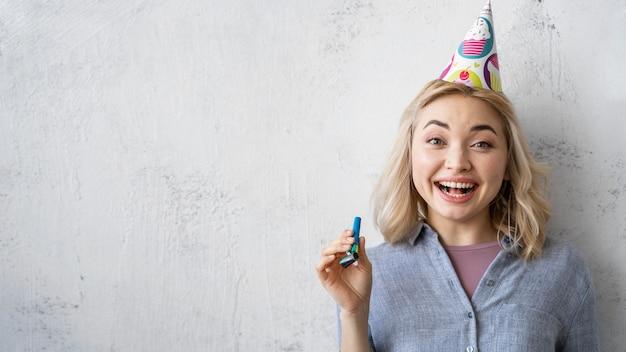Vooraanzicht van gelukkige vrouw met feestmuts en kopieer de ruimte Gratis Foto
