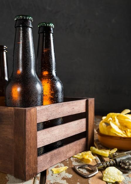 Vooraanzicht van glazen bierflessen in krat met chips Gratis Foto
