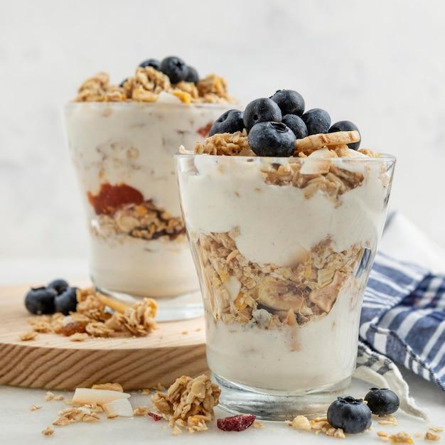 Vooraanzicht van glazen met yoghurt en ontbijtgranen Gratis Foto