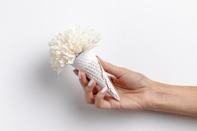 Vooraanzicht van hand - gehouden roomijskegel met bloem Gratis Foto