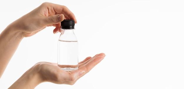 Vooraanzicht van handen met fles vloeistof Gratis Foto