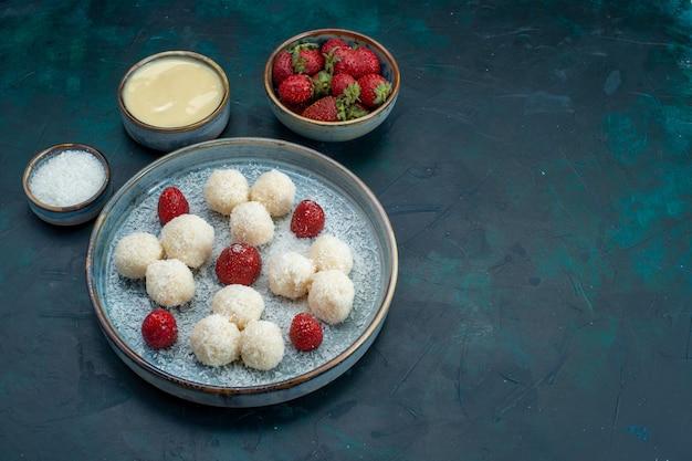 Vooraanzicht van heerlijke kokosnootsuikergoed met aardbeien Gratis Foto