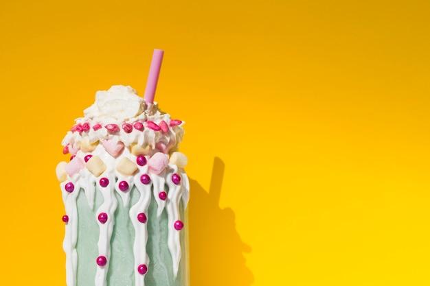 Vooraanzicht van heerlijke milkshake met gele achtergrond Gratis Foto