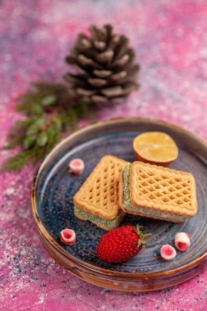 Vooraanzicht van heerlijke wafelsandwiches op roze oppervlakte Gratis Foto