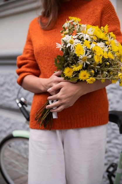 Vooraanzicht van het boeket van de vrouwenholding van bloemen met fiets Gratis Foto