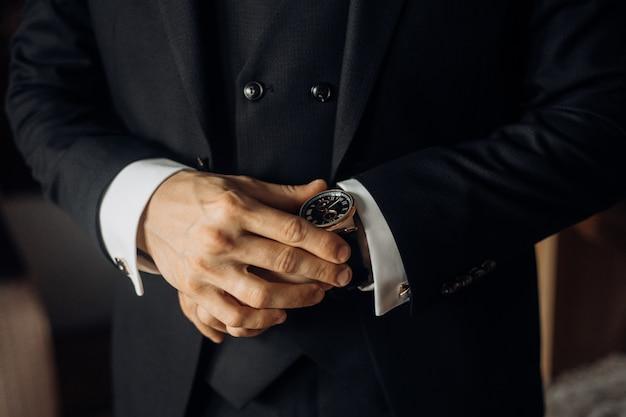 Vooraanzicht van het borstgedeelte van een man gekleed in stijlvol zwart pak en kostbaar horloge, man handen Gratis Foto