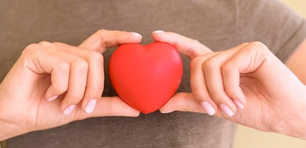 Vooraanzicht van het hartvorm van de vrouwenholding in handen Gratis Foto